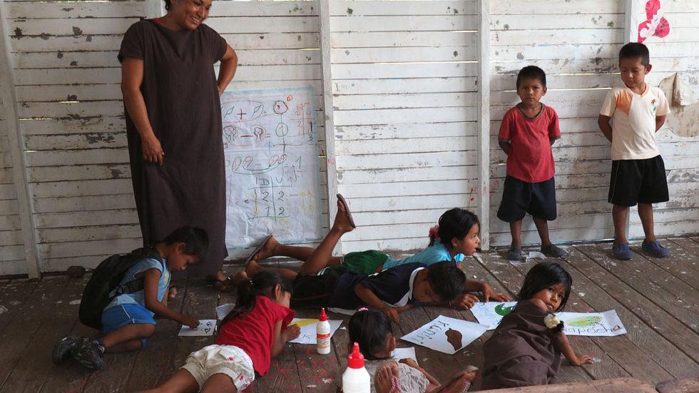 Die Kinder der Vorschulklasse malen auf dem Boden liegend