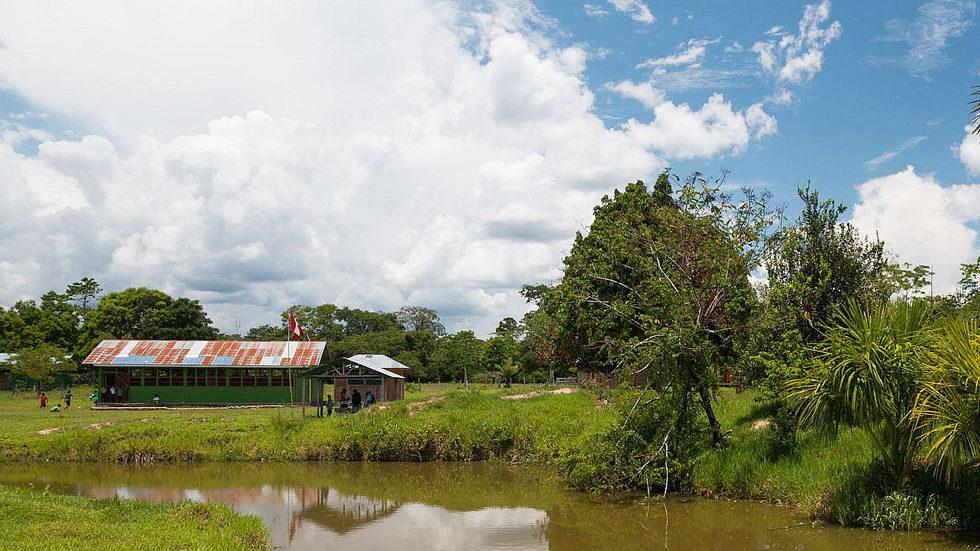 Die Schule vom Fischteich der Gemeinde aus gesehen (Foto: Konrad Wothe)