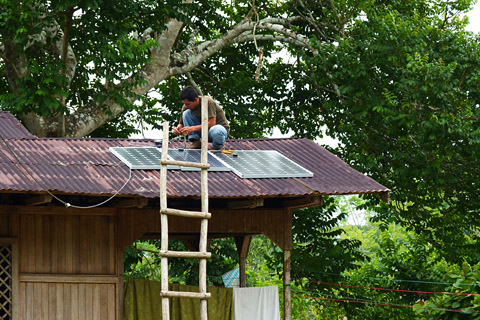 A technician from Pucallpa checks the wiring of rooftop solar panels